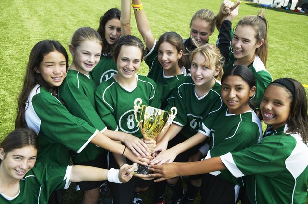 Girls (12-15) football team holding trophy, smiling, elevated view