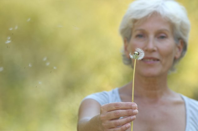 Mature woman holding dandelion, seeds blowing in breeze