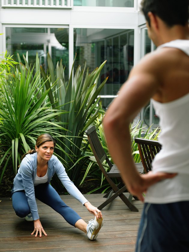 Woman performing leg stretch in garden, man standing in foreground