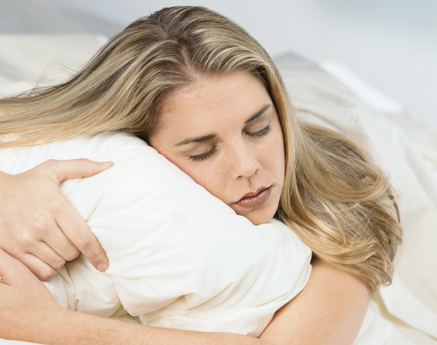 blonde caucasian woman sleeping naked in bed with a white pillow