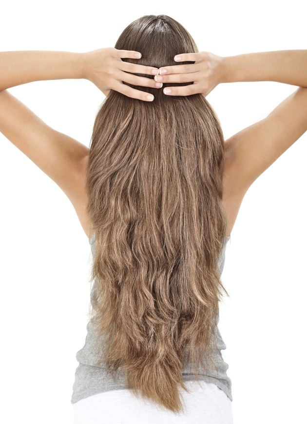 Brunette lady holding long hairs, view from back side