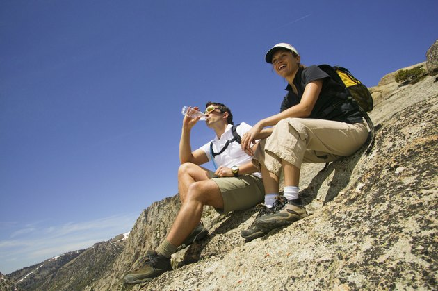 Backpacking couple sitting on mountainside