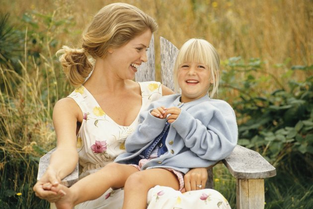 Mother and daughter (4-5) sitting outdoors on wooden chair, laughing
