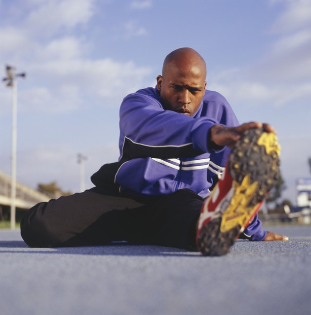 Male athlete stretching on track in stadium, ground view