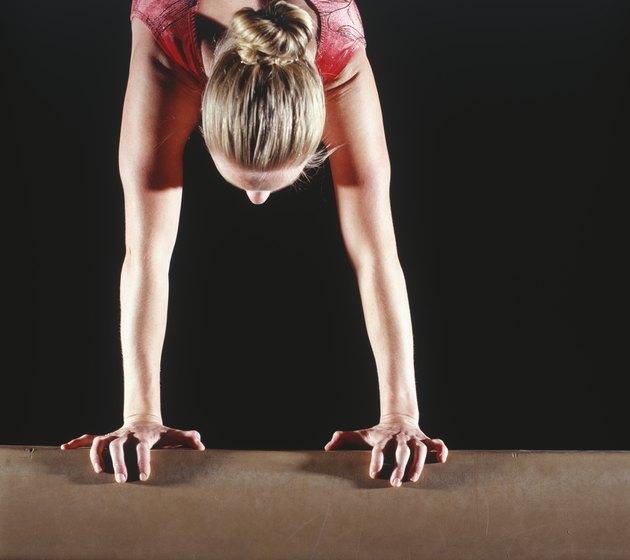 Female gymnast performing handstand on balance beam