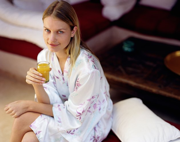 Young woman in bathrobe holding glass of juice, smiling, portrait