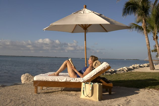 Mature woman reclining on sun lounger holding book, eyes closed