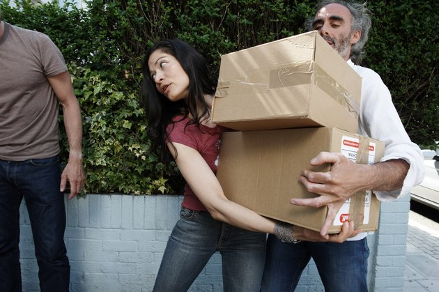 Three friends carrying cardboard boxes outside house