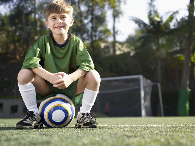 Boy sitting on soccer ball (portrait, low angle view)