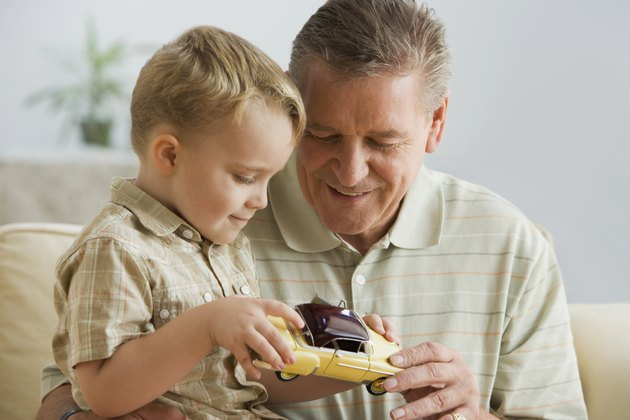 Grandfather and grandson looking at toy car