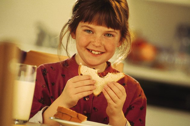 Girl eating a peanut butter and jelly sandwich