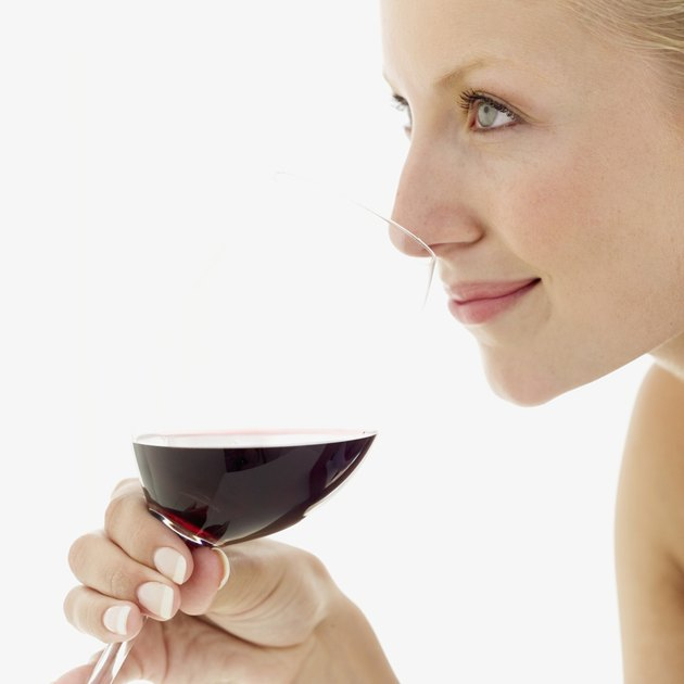 close-up of a young woman holding a glass of red wine