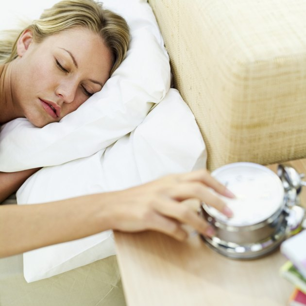 sleeping woman with her hand on an alarm clock