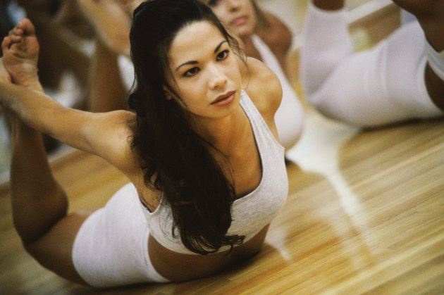 Close-up of a young woman stretching on the floor