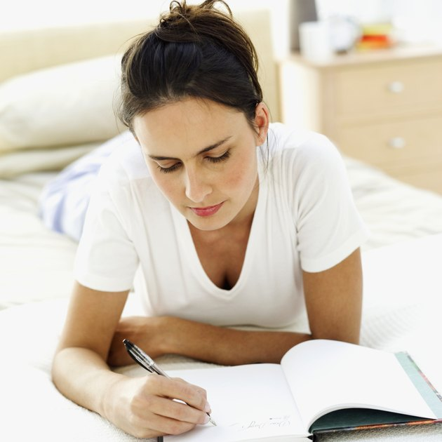 close-up of a young woman lying on the bed writing in a notebook