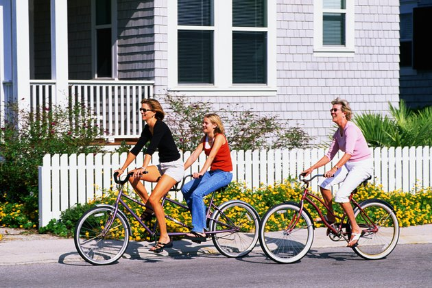 adult woman and teenage girl riding a bicycle built for two down a street by a beach house, mature adult female is behind them also riding a bike.