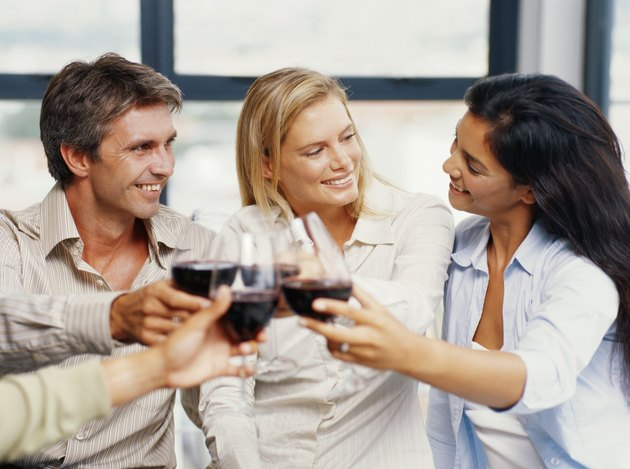 Two young couple toasting red wine in restaurant