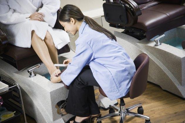 Asian nail technician filing client's toenails
