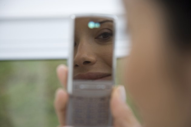 Reflection of  young woman in mobile phone