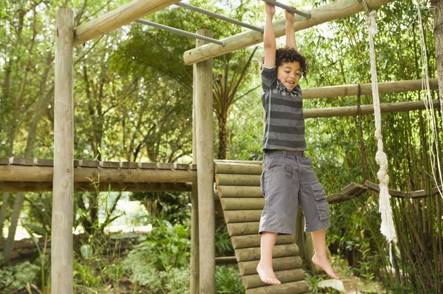 Boy hanging from jungle gym