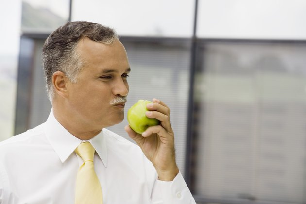 Close-up of a mature man eating an apple
