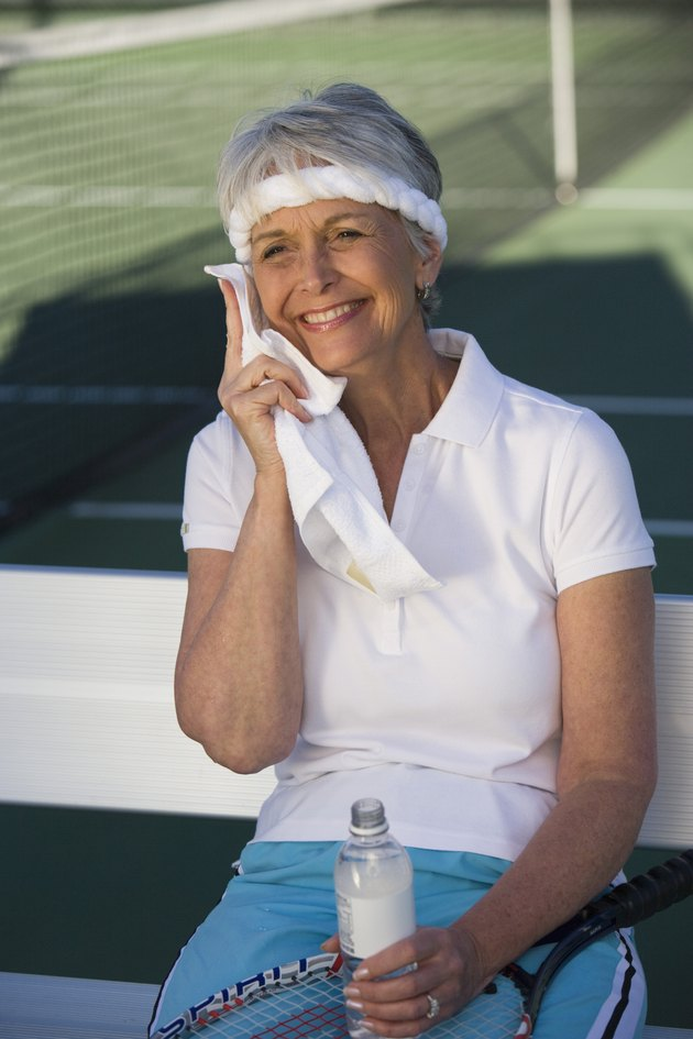 Female tennis player toweling face