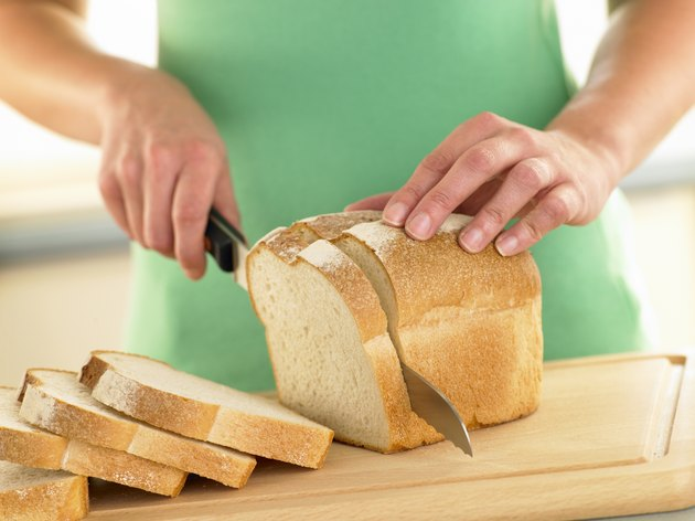 Woman Slicing A Loaf Of White Bread