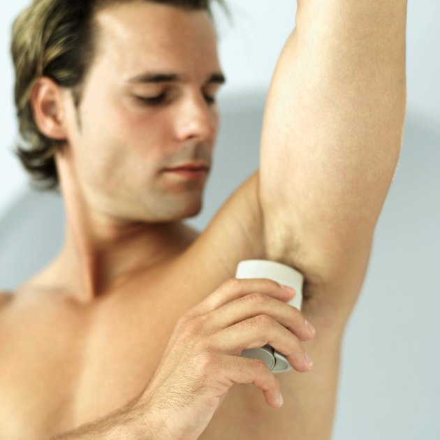man applying deodorant to his armpit