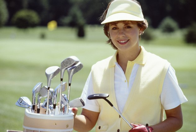 Portrait of woman posing by bag of golf clubs