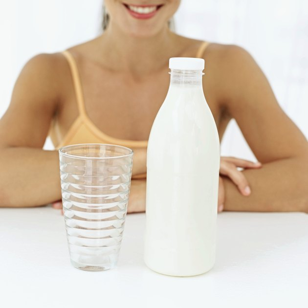 A woman sitting in front of a glass and a bottle of milk