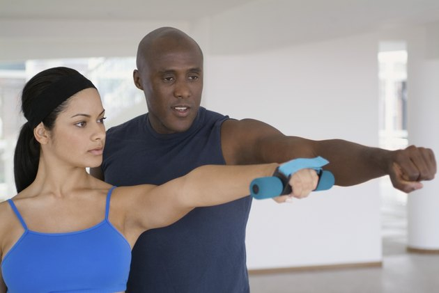 Young woman exercising with a trainer