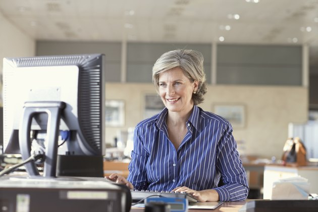 Mature businesswoman using computer in office, smiling