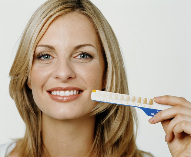 Woman holding up tooth whitening chart, smiling, portrait, close-up