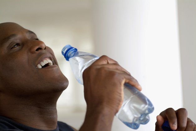 Close-up of a man drinking water from a bottle