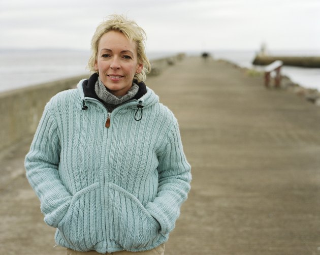 Mature woman outdoors by sea, smiling, portrait