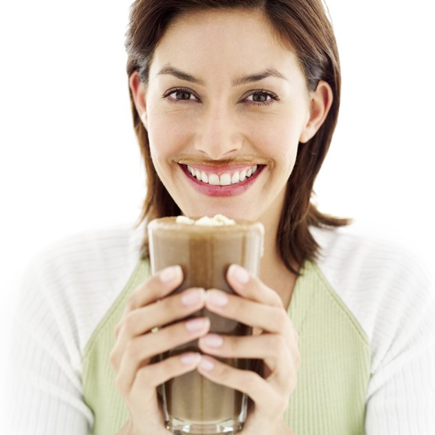 portrait of a young woman drinking a chocolate milkshake