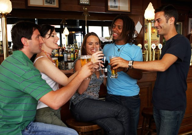 Group of people raising glasses together in bar