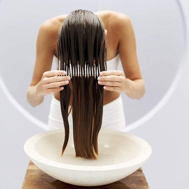 woman combing wet hair over a washbasin