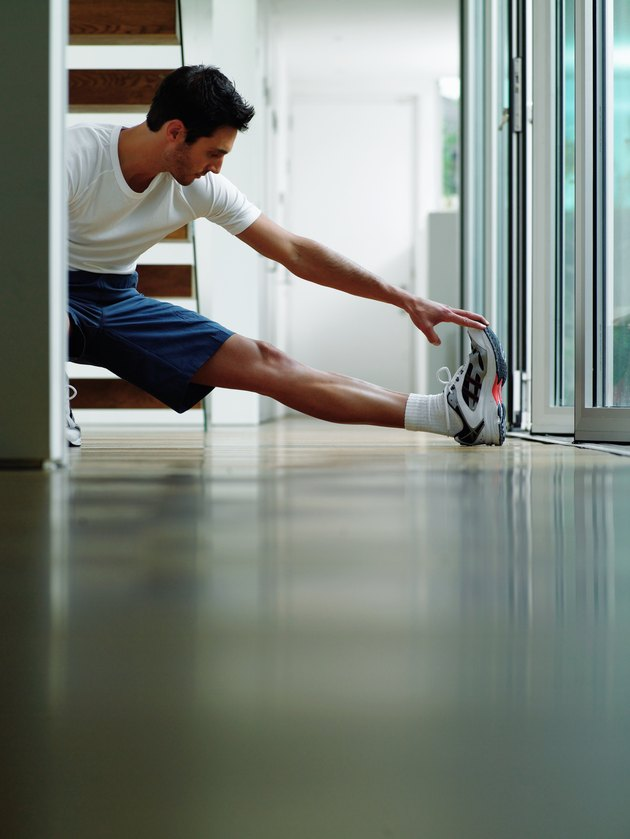 Man in sports clothes performing leg stretch in hallway, ground view