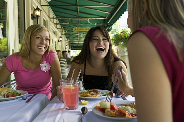lifestyle portrait of a group of three teenage female friends as they eat at a sidewalk cafe