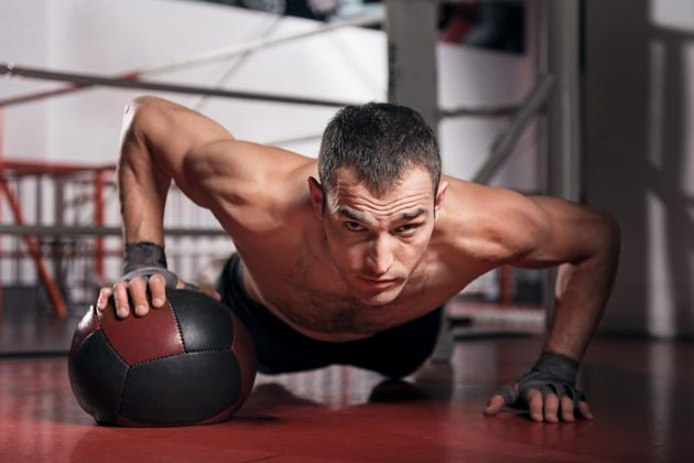 Do your best. Muscular man doing push-up with the help of special fitness ball and looking forward.