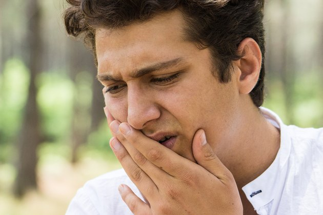 Man feeling toothache and holding his jaw