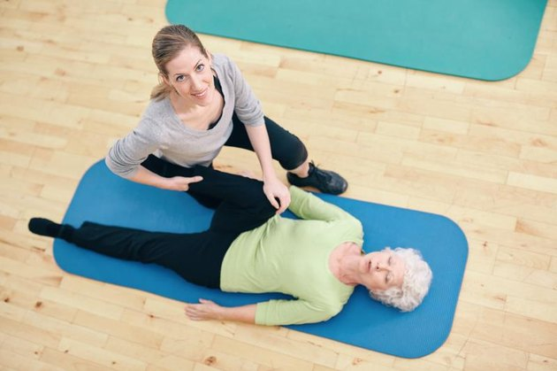 Top view of physical therapist helping senior woman do leg stretches at health center. Gym trainer assisting elder woman in leg stretching workout.