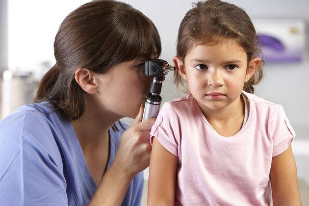 Doctor Examining Child's Ears In Doctor's Office