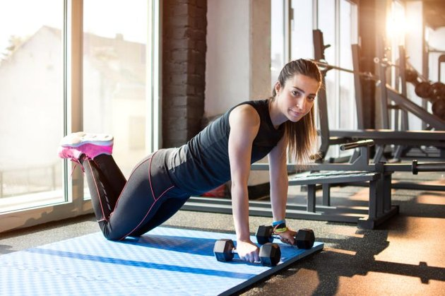 Young woman doing plank exercise with hand weights in gym.
