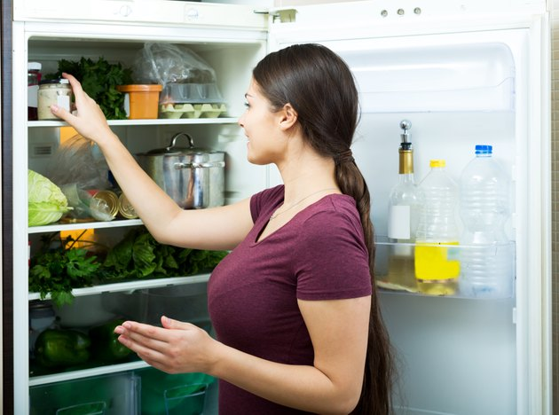 Positive housewife standing near filled fridge