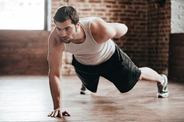 Confident muscled young man wearing sport wear and doing one hand push-up while exercising on the floor in loft interior