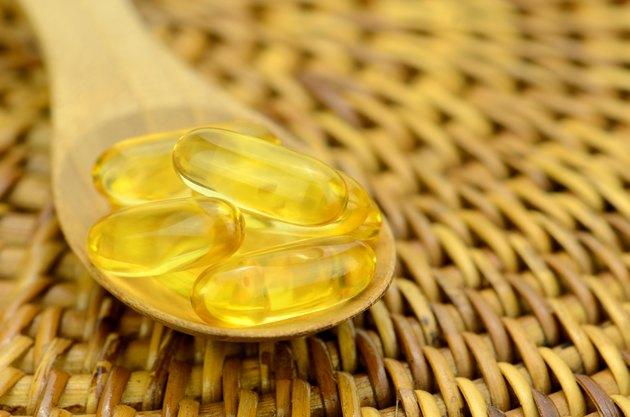 Spoonful of fish oil capsule.