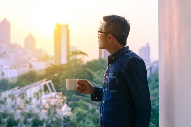 Businessman in denim jacket and glasses drinking hot coffee.