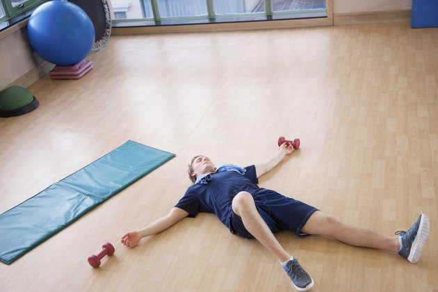 Tired young man lying on his back in the gym